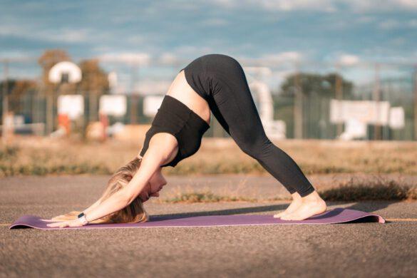 Junge Frau in Yoga Asana herabschauender Hund
