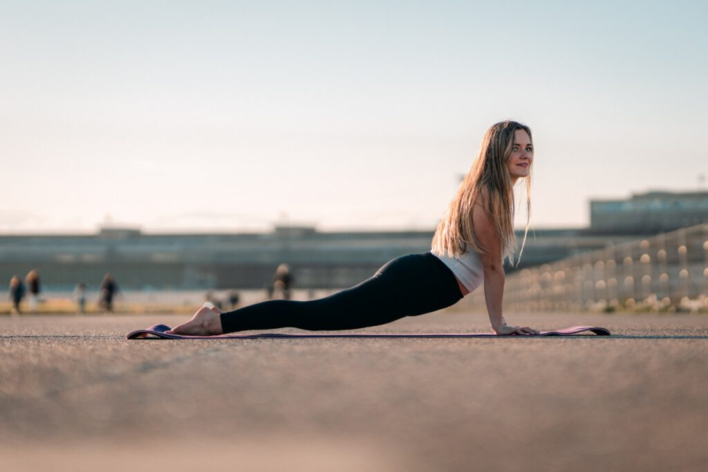 junge Frau im heraufschauendem Hund Yoga Asana