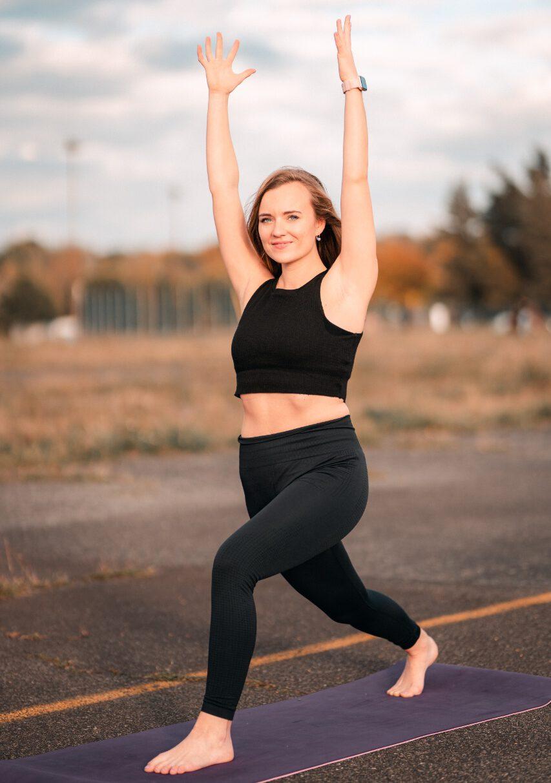 Junge Frau in Yoga Asana Krieger eins